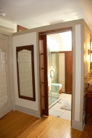 The bathroom has a french pocket door
